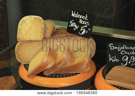 Traditional Dutch cheeses on display in a store (text on labels: price and product information in Dutch)