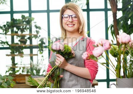 Young girl florist with glasses