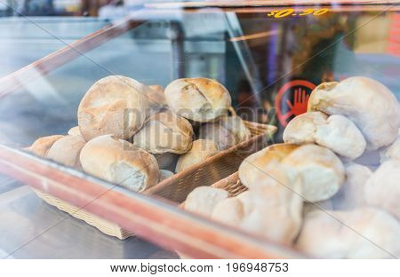 Closeup Of Fresh White Bread Rolls Buns Behind Window Glass Of Bakery
