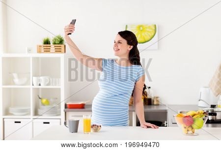 pregnancy, people and technology concept - happy pregnant woman with smartphone taking selfie and having breakfast at home kitchen