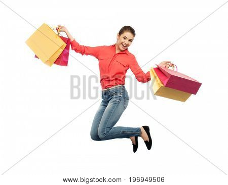 sale, motion and people concept - smiling young woman with shopping bags jumping in air over white background