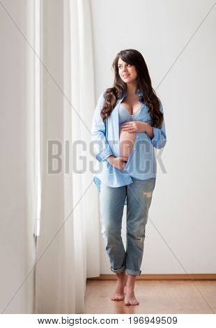 pregnancy, motherhood, people and expectation concept - happy pregnant woman with big bare tummy looking through window at home