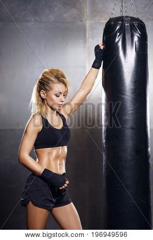 Fit and sporty young girl having a kickboxing training. Underground gym. Health, sport, fitness concept.