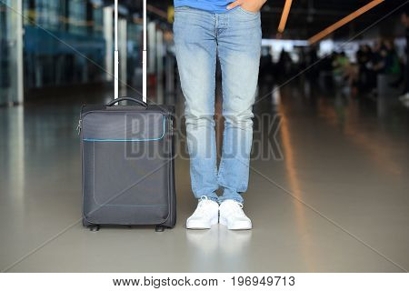 Man in blue jeans with suitcase in airport. Passenger traffic theme.