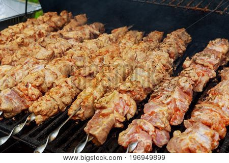 Grilled Shish Kebab On Metal Skewer. Chef Hands Cooking Roasted Meat Barbecue With Lots Of Smoke.
