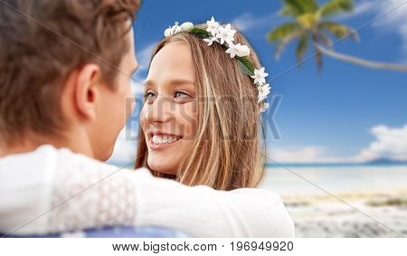 summer holidays, love, romance and people concept - happy smiling young hippie couple hugging over tropical beach background