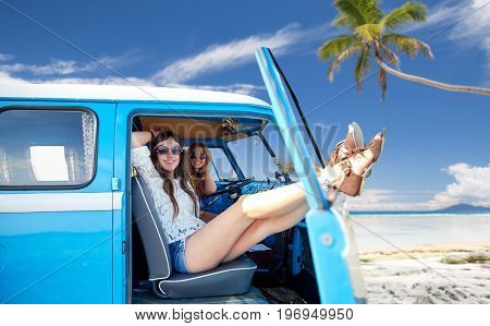 summer holidays, road trip, travel and people concept - smiling young hippie women resting in minivan car over tropical beach background