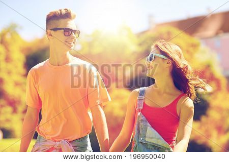 holidays, vacation, love and people concept - happy smiling teenage couple walking and looking at each other in summer park