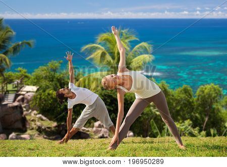 fitness, sport and people concept - happy couple doing yoga outdoors over natural background and sea