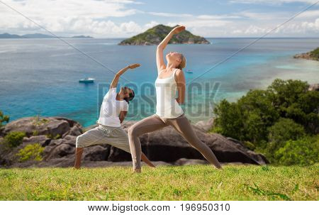 fitness, sport, people and healthy lifestyle concept - couple doing yoga in warrior pose over natural background and sea