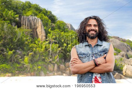 travel, tourism and people concept - smiling young hippie man in denim vest over tropical island beach background