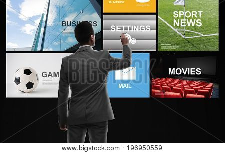 business, people, mass media and technology concept - businessman with marker and virtual screen from back over black background
