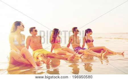 friendship, sea, summer vacation, holidays and people concept - group of smiling friends wearing swimwear and sunglasses sitting in water on beach