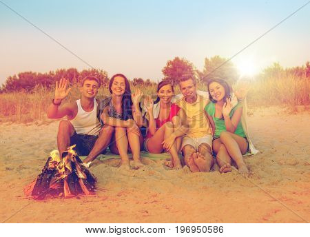 friendship, summer vacation, holidays, gesture and people concept - group of smiling friends sitting near fire and waving hands on beach