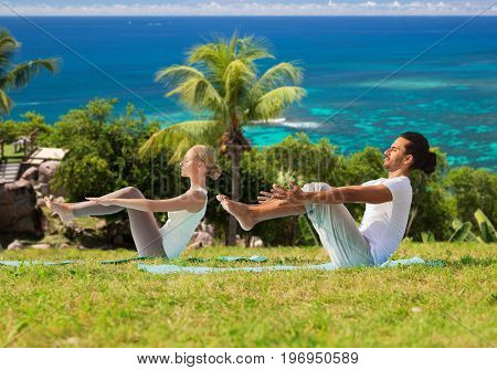 fitness, sport, relax and people concept - couple making yoga half-boat pose over natural background