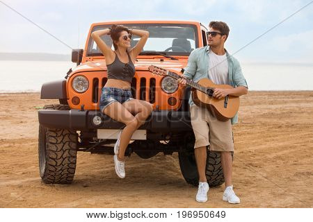 Happy young couple resting at the beach with a guitar while standing near their car