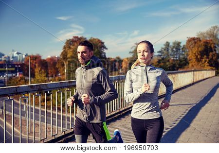 fitness, sport, people and jogging concept - happy couple running outdoors