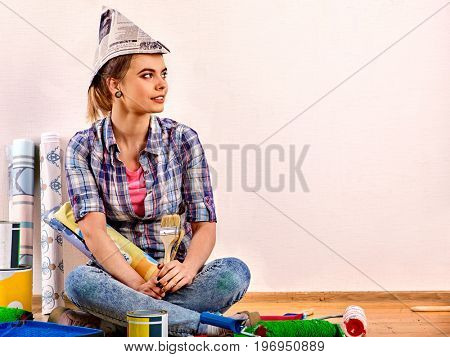 Repair home woman holding paint roller for wallpaper. Aggressive screaming girl in newspaper cap renovation apartment on isolated. Tired of work as student. Moving to a new house.