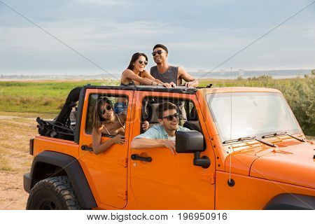 Cheerful young people having fun be travelling together by a car