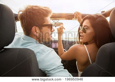 Happy cheerful couple having fun while sitting in a car