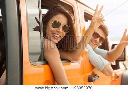 Happy friends sitting in a car and showing peace gesture outdoors