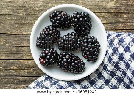 Tasty ripe blackberries in bowl on wooden table.