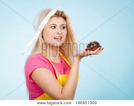 Baking tasty desserts sweets at home concept. Woman holding delicious sweet chocolate cupcake wearing apron and colander on head as hat.