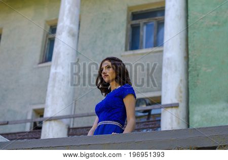 A graceful girl in a blue dress looks into the distance, standing on the balcony of the old building.