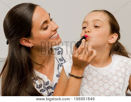 Mother playing with her daughter applying lipstick