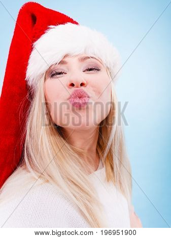 Woman wearing Santa Claus hat making funny face expressions. Christmas fun and celebration concept. Studio shot on blue background.