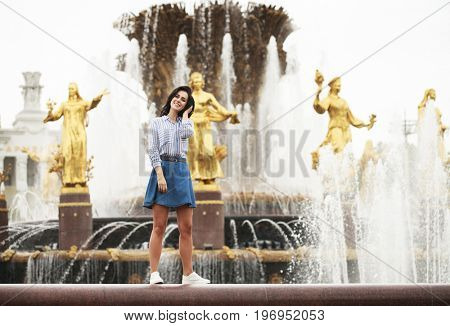 Young beautiful brunette girl posing near city fountain in blue shirt and skirt