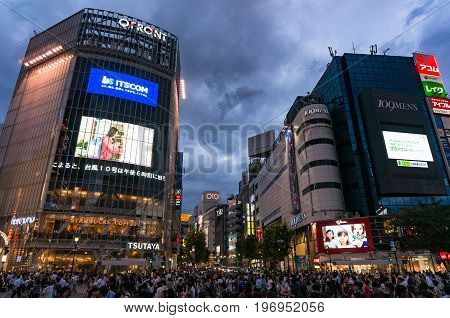 Crowd Of Tourists And Locals On Famous Shibuya Crossing In Tokyo At Night