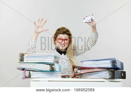 Mobbing at work bad job relations concept. Angry mad bossy businesswoman being furious sitting working at desk throwing paper