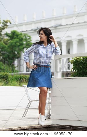 Young beautiful brunette woman posing in striped shirt and blue skirt, street summer outdoors