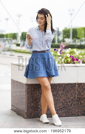 Beautiful young brunette woman calling by phone in summer park