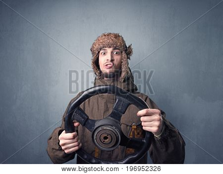 Young man holding black steering wheel on a blueish gray background