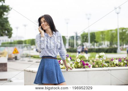 Close up portrait of young beautiful brunette woman in blue jeans skirt calling by phone in summer street