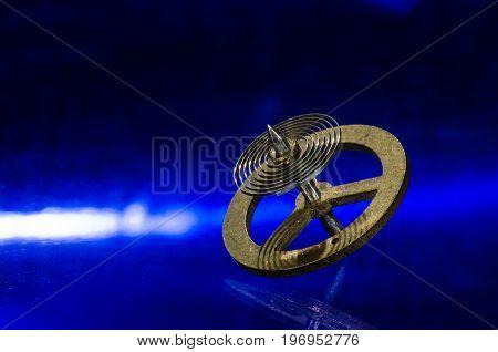 Watch Repair: Vintage Pocket Watch Hairspring Resting on a Blue Surface
