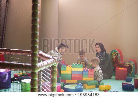 young happy parents having fun with kids in children playground indoor