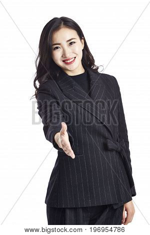 young asian businesswoman in formal wear reaching out for a handshake happy and smiling studio shot isolated on white backround.