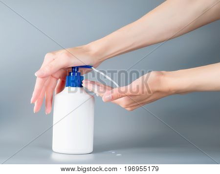 Woman hands pouring liquid soap from dispenser. On gray background