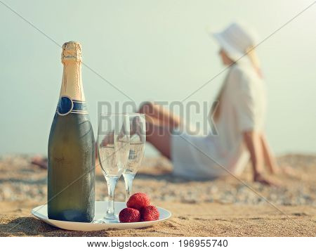 A bottle of sparkling wine with glasses on a white plate. Sandy summer beach in the sun.