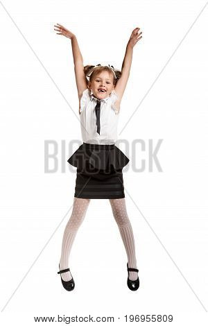 Happy smiling schoolgirl jumping and laughing on white background