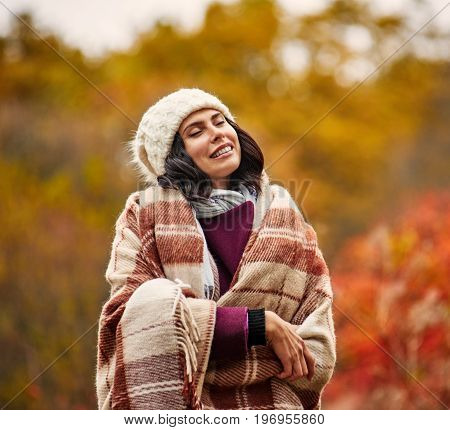 Smiling sensual woman basking with plaid in autumn park