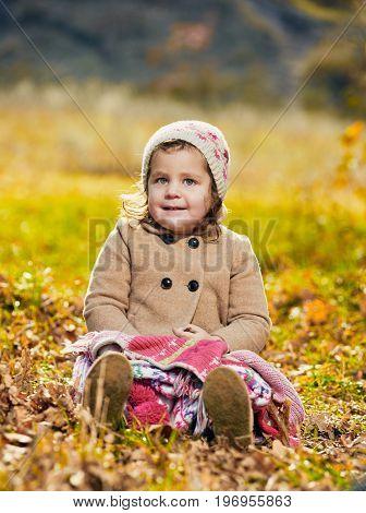 Portrait of cute little girl sitting on grass in autumn park