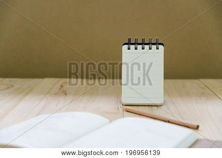 Small note book paper (notepad) stand for writing information with pencil and book on wood table
