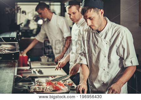 Food concept. Three young chefs in white uniform decorate ready dish in restaurant. They are working on maki rolls. Preparing traditional japanese sushi set in interior of modern professional kitchen