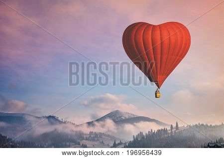 Beautiful red air balloon heart shape against blue and pink pastel sky in a sunny bright morning. Foggy mountains in the background. Romantic trip on Valentine's Day. Sport and recreation travel theme