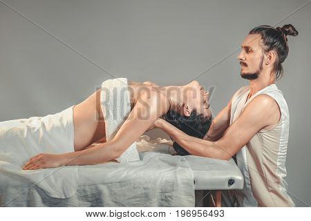 Massage stretching therapy. A young professional male masseur makes Thai massage. Patient woman is lying down on a bed and is covered with white towel. Treatment, rest, relaxation, spa. Studio shot