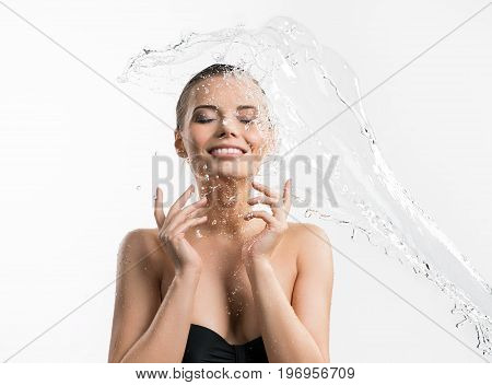 Young beautiful girl her eyes shut enjoying water stream and splashes falling from the side on her head and shoulder studio shot